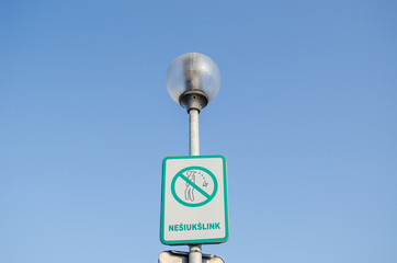 warning sign on littering streets on street lamp