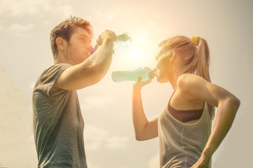 Couple drink water after running