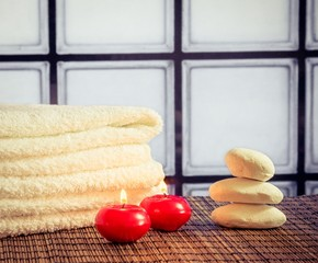 Spa massage with towel stacked stone red candles warm atmosphere