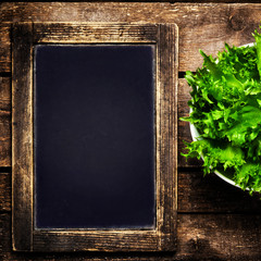 Black chalkboard for menu and fresh salad over wooden background