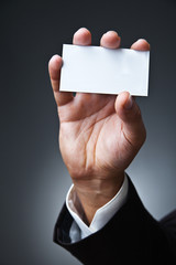 business man show card on dark grey