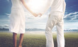 Couple in love holding hands on a green field