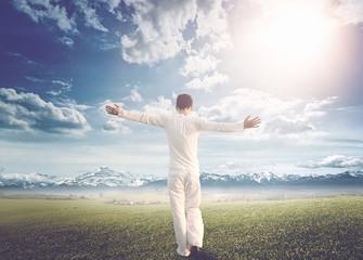 Man walking on a meadow towards a mountain range