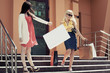 Two young fashion women with shopping bags on the mall steps