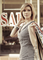 Happy young woman with shopping bags at the mall windows