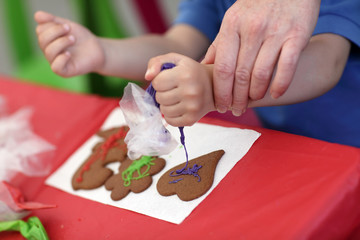 Mother and son decorating gingerbread shapes