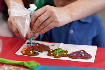 Mother with son decorating gingerbread shapes