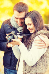 couple with photo camera in autumn park