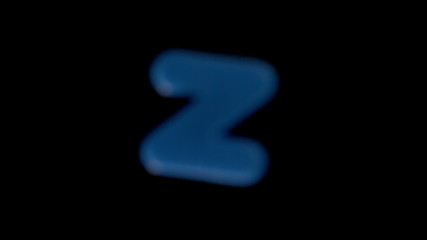 The letter z coming into focus on black background