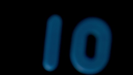 The number ten coming into focus on black background