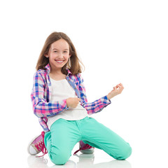 Smiling girl playing the air guitar