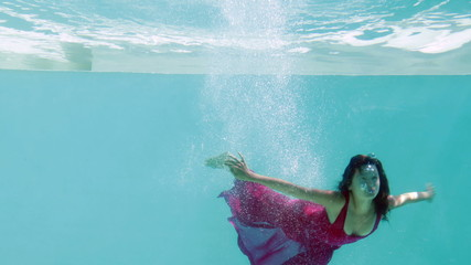 Brunette in evening gown diving into swimming pool