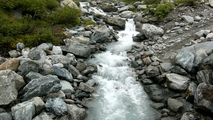 Rapids on quick mountain torrent in Alps, water is flowing