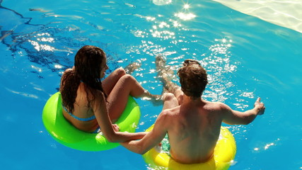 Couple sitting on inflatable rings in the swimming pool