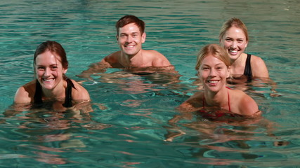Four smiling people doing water aerobics in swimming pool