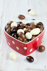 chocolate covered nuts and raisins in a heart-shaped bowl on woo