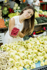 Young woman buying raspberries at the market