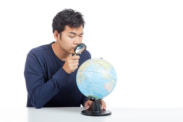 Asian man use magnifying glass searching on a world globe
