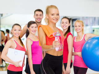 smiling sporty woman with water bottle and towel