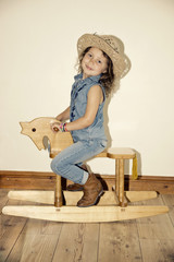 girl playing on a wooden rocking horse