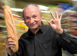 Happy senior man holding fresh baguette