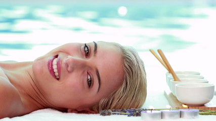 Peaceful smiling blonde lying on massage table poolside