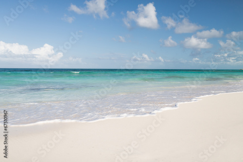 Leinwanddruck Bild blue sea or ocean, white sand and sky with clouds