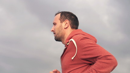 Young man jogging against cloudy sky
