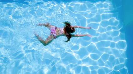 Overhead of brunette swimming in pool on sunny day