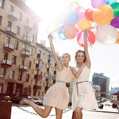 two beautiful ladys in retro outfit holding a bunch of balloons