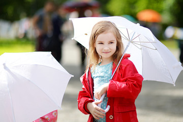 Adorable little girl at rainy day in autumn