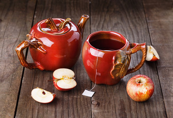 Apple tea and apples over rustic wooden background