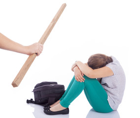 Male hand holding a wooden stick to beaten on a little girl, iso