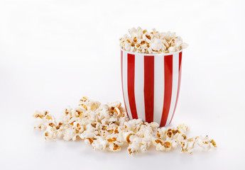 Buttered popcorn in a striped bowl over white background