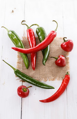 Colorful chilli peppers over white wooden background