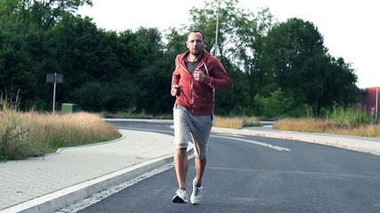 Jogger running on asphalt road, super slow motion