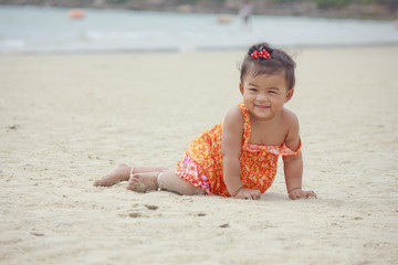 Asian baby smiling on beach sand