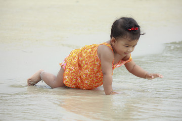 Asian baby smile for the first time with the sea.