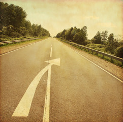 Country road with arrow sign on asphalt in grunge and retro styl