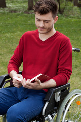 Disabled reading a book outdoors