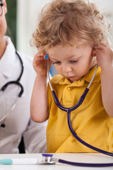Boy with curly blond hair playing with stethoscope