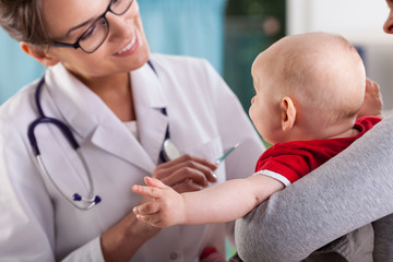 Pediatrician doctor examining little baby