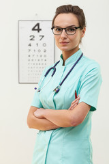 Confident female optometrist standing with arms crossed