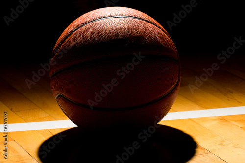 Plexiglas Basketball on court black background with light effect