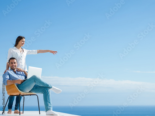 canvas print picture relaxed young couple working on laptop computer at home