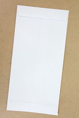 Blank white paper envelope on brown background