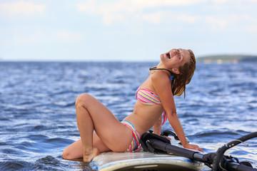 Happy windsurfer sitting on the board