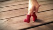 canvas print picture - Hand in red felt boots is walking on wooden table