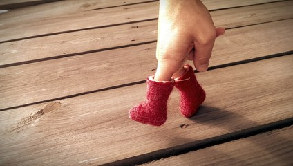 Hand in red felt boots is walking on wooden table