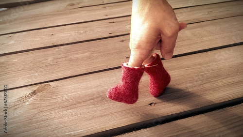 canvas print picture Hand in red felt boots is walking on wooden table